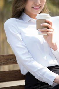 Cheerful young Chinese businesswoman drinking coffeeの写真素材 [FYI02230085]