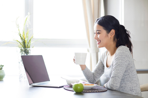 Young woman using laptop while having breakfastの写真素材 [FYI02230119]