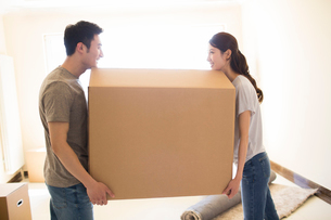 Happy young Chinese couple moving to a new houseの写真素材 [FYI02230125]