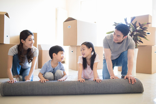 Happy young Chinese family unrolling carpet in new houseの写真素材 [FYI02230143]