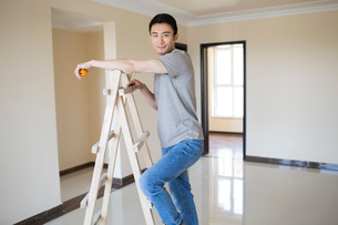 Young Chinese man working on home renovationの写真素材 [FYI02230144]