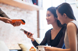 Chinese friends paying with smart phone in cafeの写真素材 [FYI02230164]