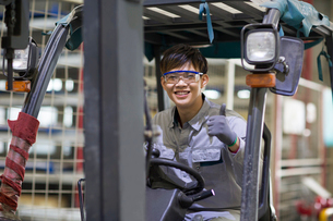 Young workman driving forklift in the factoryの写真素材 [FYI02230198]