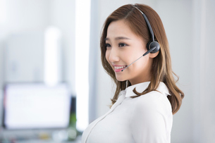 Cheerful young Chinese businesswoman with headset in officeの写真素材 [FYI02230214]