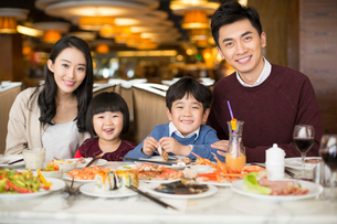 Cheerful young Chinese family having buffet dinnerの写真素材 [FYI02230217]