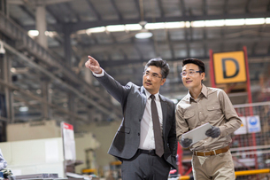 Businessman and engineer talking in the factoryの写真素材 [FYI02230221]