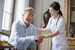 Nursing assistant taking care of senior manの写真素材 [FYI02230223]