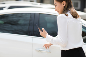Young businesswoman opening car doorの写真素材 [FYI02230225]