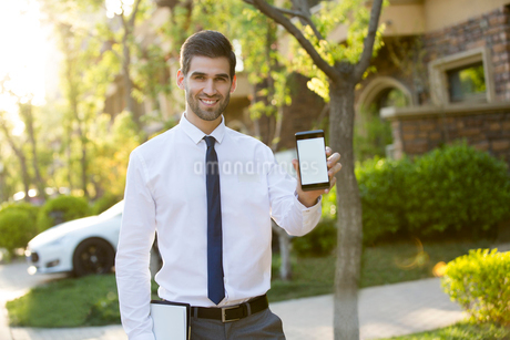 Confident businessman showing smart phoneの写真素材 [FYI02230245]