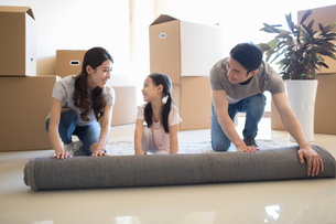 Happy young Chinese family unrolling carpet in new houseの写真素材 [FYI02230249]