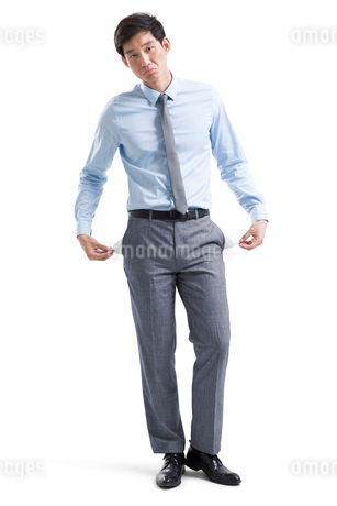 Young Chinese businessman showing empty pocketsの写真素材 [FYI02230269]