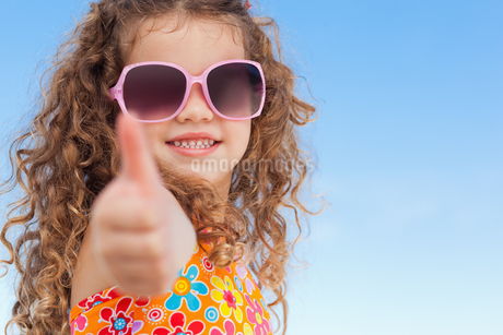 Little girl with sunglasses on the beach giving thumb upの写真素材 [FYI02230275]