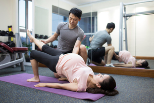 Pregnant woman working with trainer at gymの写真素材 [FYI02230289]