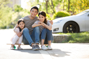 Happy young Chinese family sitting on a skateboardの写真素材 [FYI02230296]