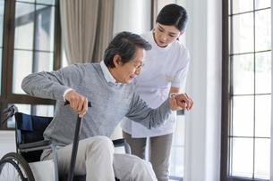 Nursing assistant taking care of senior man in wheel chairの写真素材 [FYI02230302]