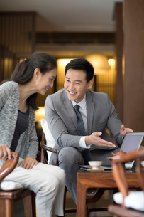 Confident Chinese businessman talking with a mature womanの写真素材 [FYI02230303]