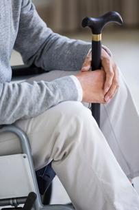 Senior man in wheelchair holding a caneの写真素材 [FYI02230305]