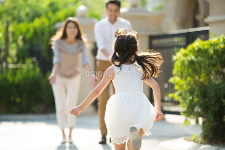 Happy little Chinese girl running towards her parentsの写真素材 [FYI02230361]