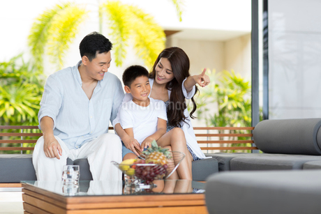 Happy young Chinese family sitting on the sofaの写真素材 [FYI02230403]