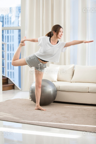 Young Chinese woman practicing yoga at homeの写真素材 [FYI02230424]