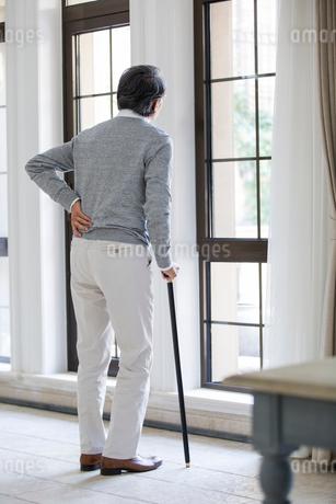Senior man looking out windowの写真素材 [FYI02230477]