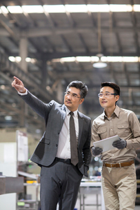 Businessman and engineer talking in the factoryの写真素材 [FYI02230515]