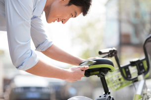 Young man scanning a QR code to unlock a share bikeの写真素材 [FYI02230524]