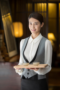 Elegance Chinese waitress holding two cups of teaの写真素材 [FYI02230530]