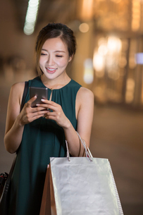 Cheerful young Chinese woman shoppingの写真素材 [FYI02230539]