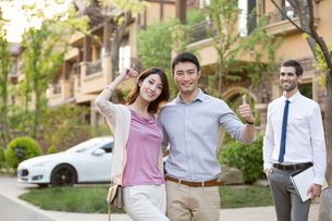 Happy young Chinese couple receiving house key from real estate agentの写真素材 [FYI02230545]