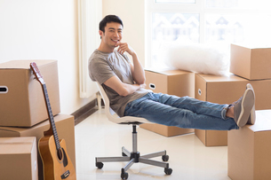 Happy young Chinese man moving to a new houseの写真素材 [FYI02230566]