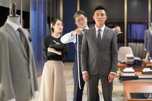 Chinese fashion designer taking measurement of customerの写真素材 [FYI02230588]