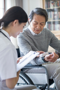 Nursing assistant taking care of senior man in wheel chairの写真素材 [FYI02230590]