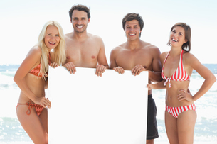 Four friends in swimsuits smiling as they hold a blank posterの写真素材 [FYI02230602]
