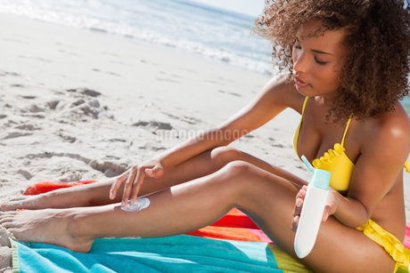 Young attractive woman attentively applying sunscreen on her legの写真素材 [FYI02230633]