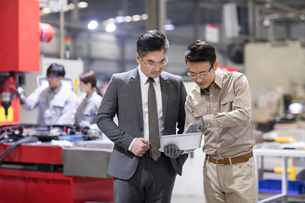 Businessman and engineer talking in the factoryの写真素材 [FYI02230640]