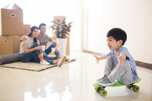 Happy young Chinese family moving to a new houseの写真素材 [FYI02230724]