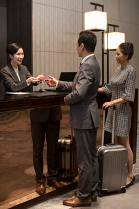 Chinese couple checking into hotelの写真素材 [FYI02230731]