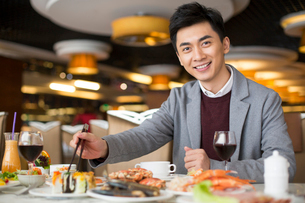 Cheerful young Chinese man having buffet dinnerの写真素材 [FYI02230735]