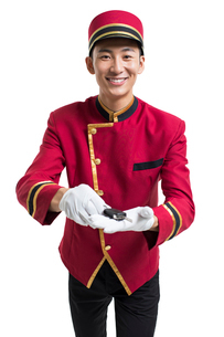 Young Chinese bellboy holding a car keyの写真素材 [FYI02230742]