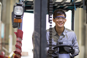 Young workman driving forklift in the factoryの写真素材 [FYI02230743]