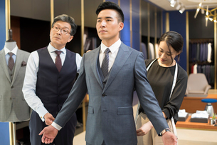 Chinese fashion designers examining suit on customerの写真素材 [FYI02230775]
