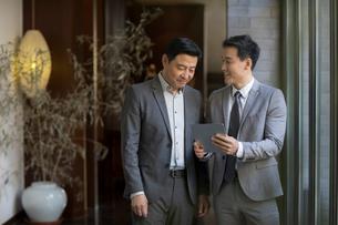 Cheerful Chinese businessmen using digital tabletの写真素材 [FYI02230780]