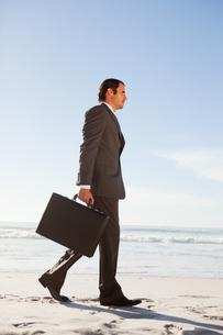 Young handsome businessman walking in front of the oceanの写真素材 [FYI02230796]