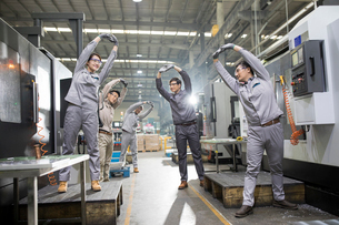 Engineers stretching in the factoryの写真素材 [FYI02230829]
