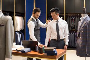 Chinese fashion designer taking measurement of customerの写真素材 [FYI02230836]
