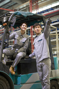 Confident workers driving forklift in the factoryの写真素材 [FYI02230840]