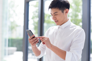 Young businessman using smart phoneの写真素材 [FYI02230850]