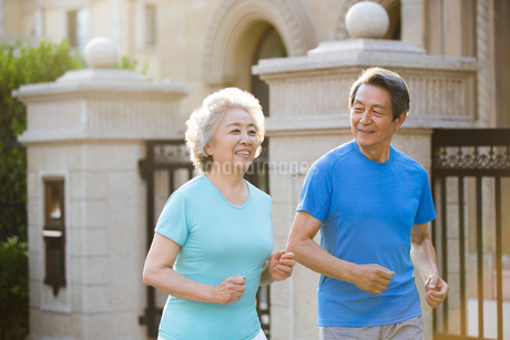Cheerful senior Chinese couple jogging outsideの写真素材 [FYI02230890]
