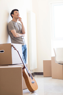 Happy young Chinese man moving to a new houseの写真素材 [FYI02230899]